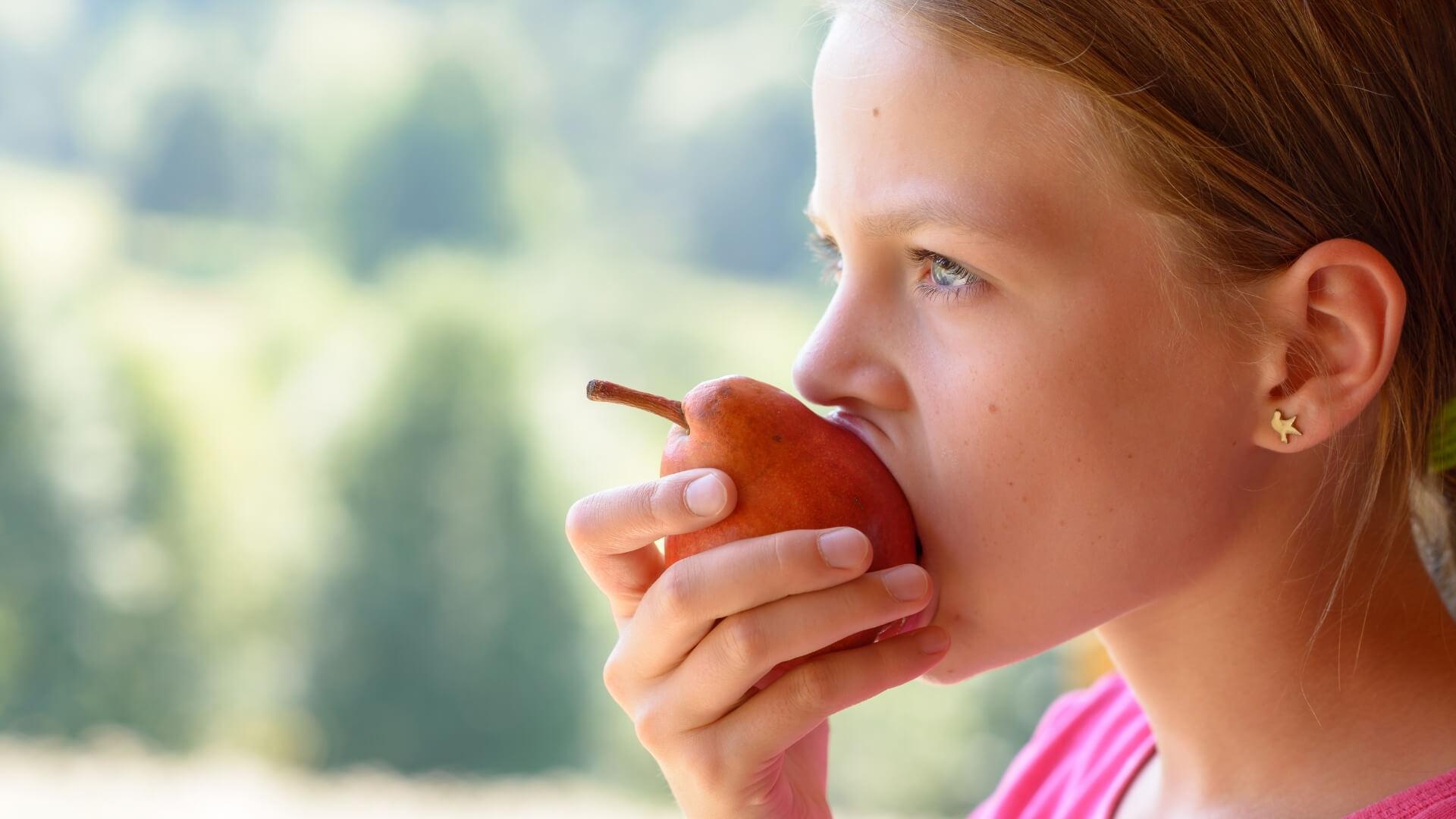 bambina che mangia una pera nel momento giusto della giornata