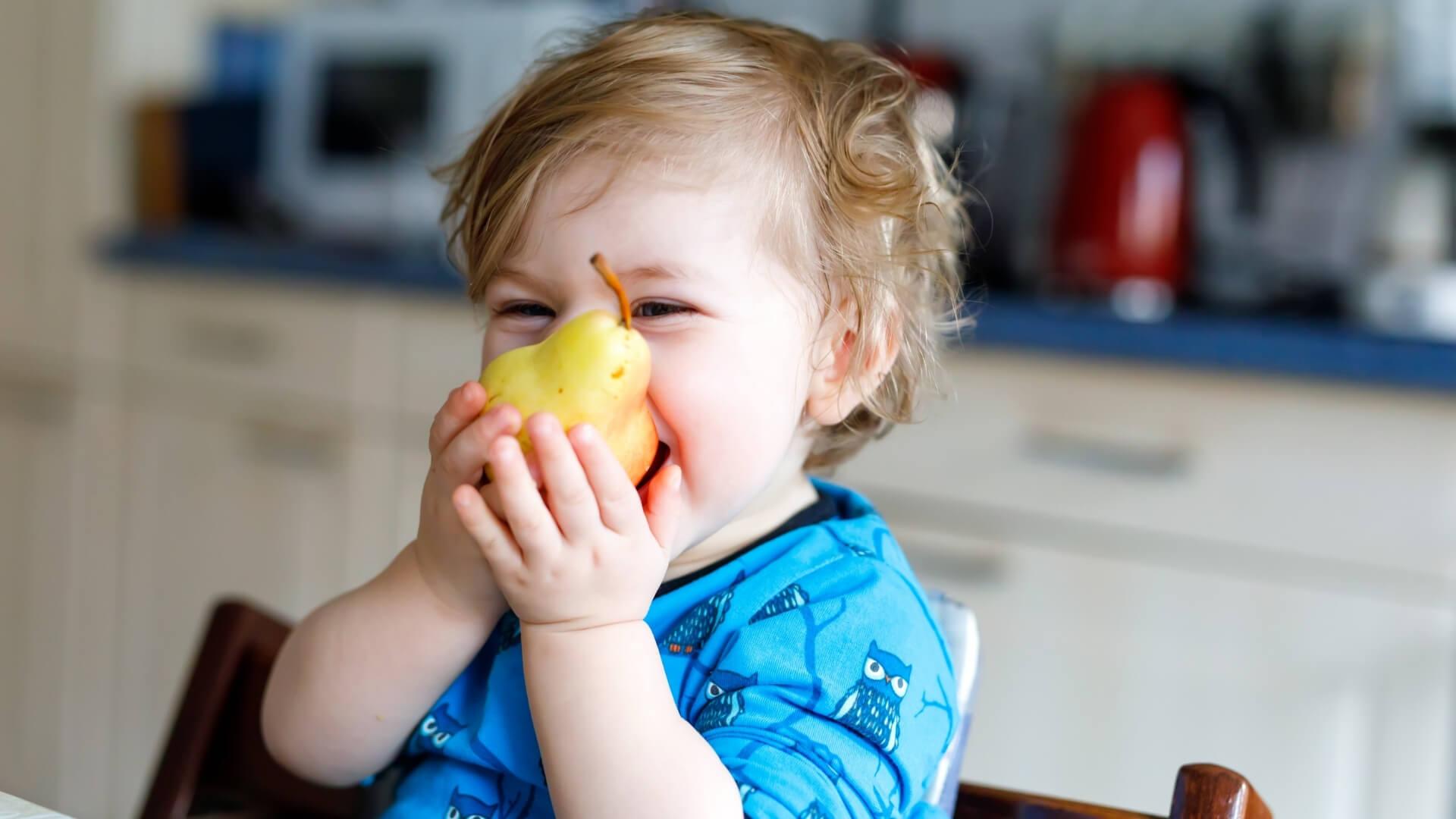 bambino che mangia una pera assaporandone il gusto